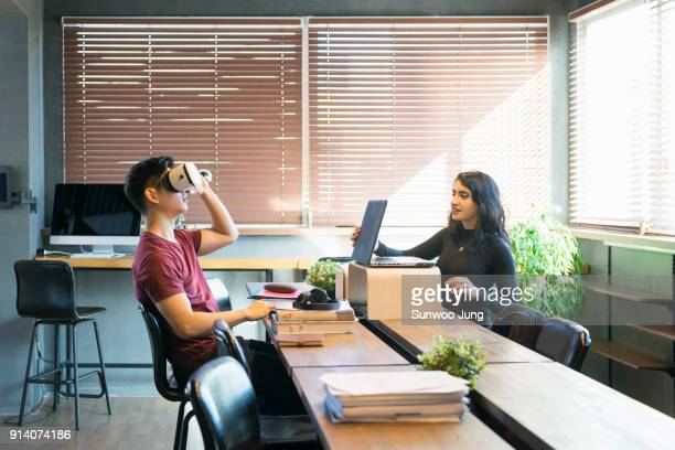 Creative workers examining VR in modern office