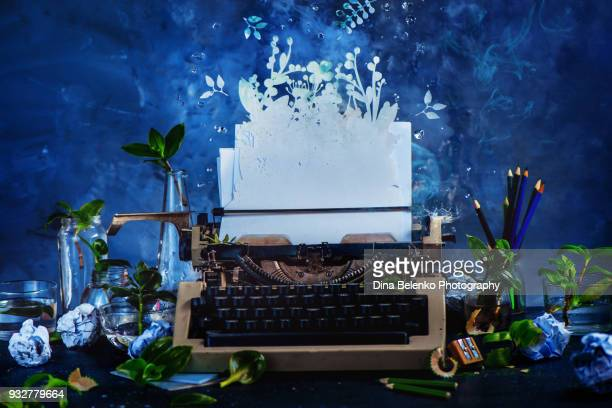 Creative writer workplace with a typewriter and growing plants. Imagination garden concept. Dark still life with action and copy space.