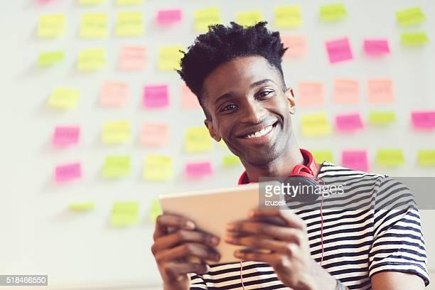 Kreative junge Afro amerikanische halten einen Tablet PC