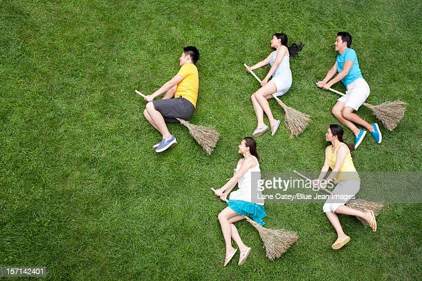 creative young people imitating flying - witch flying on broom stock photos and pictures