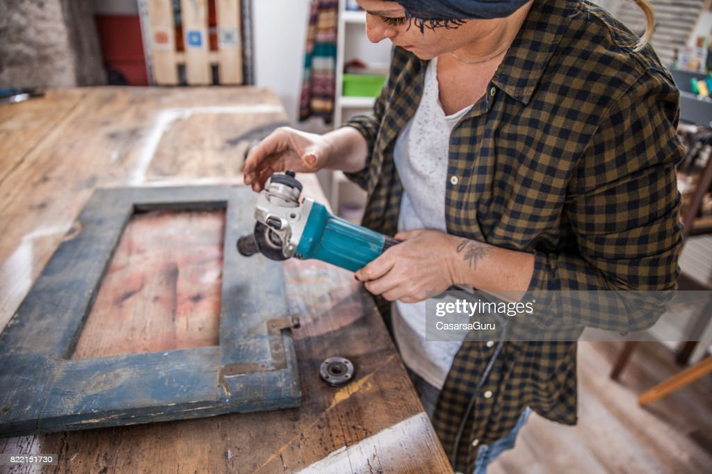 Creative Young Woman Changing the Attachment of Grinding Machine : Stock Photo