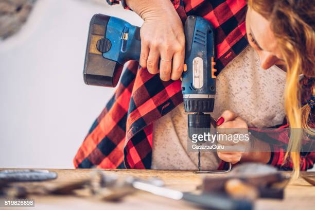 creative young woman working with drilling machine - drill stock pictures, royalty-free photos & images