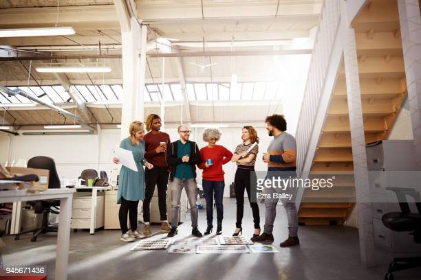 Creatives in an industrial office discussing work.