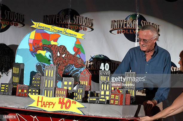 Creator Stan Lee poses by the birthday cake during the SpiderMan 40th Birthday celebration at Universal Studios on August 13 2002 in Universal City...