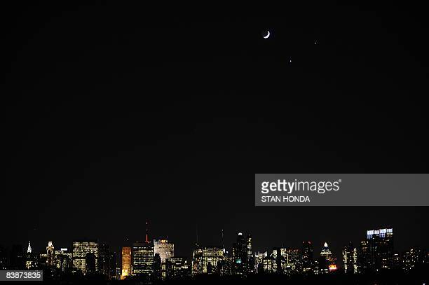 A crecent moon and the planets Venus and Jupiter are seen in a rare alignment over the Manhattan skyline in this rare alignment December 1 2008 from...