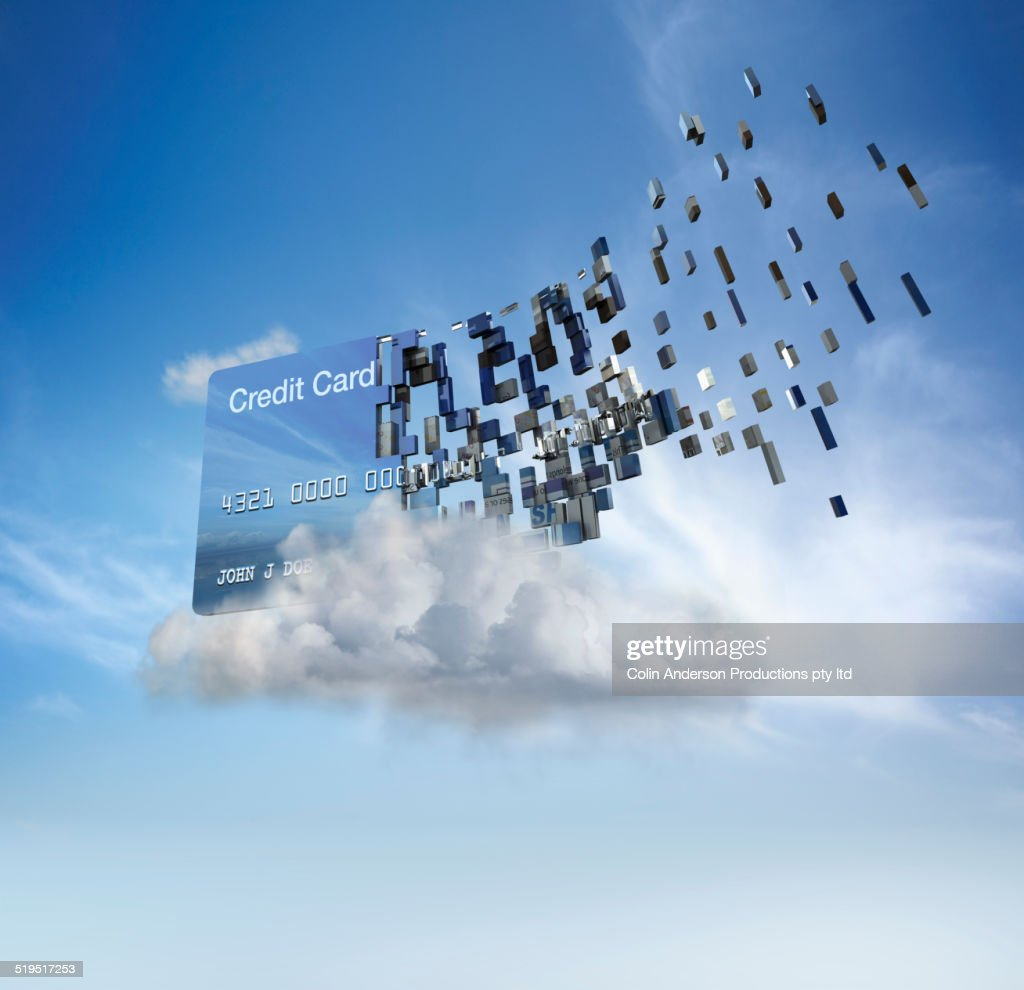 Credit card disintegrating into cloud in blue sky : Stock Photo
