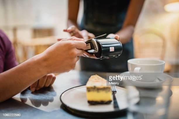 cartão de crédito pagamento sem contacto wireless no cafe - garçonete - fotografias e filmes do acervo