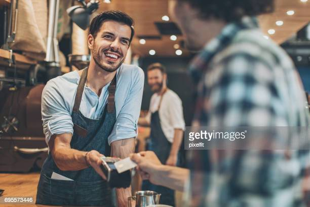 credit card payment in the coffee shop - salesman stock pictures, royalty-free photos & images