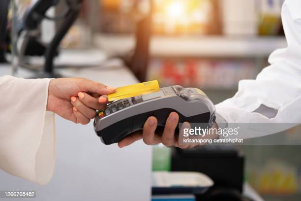 credit card payment service. customer paying for order of cheese in grocery shop.credit card payment service the customer pays to order cheese in the pharmacy. - greeting card stock pictures, royalty-free photos & images