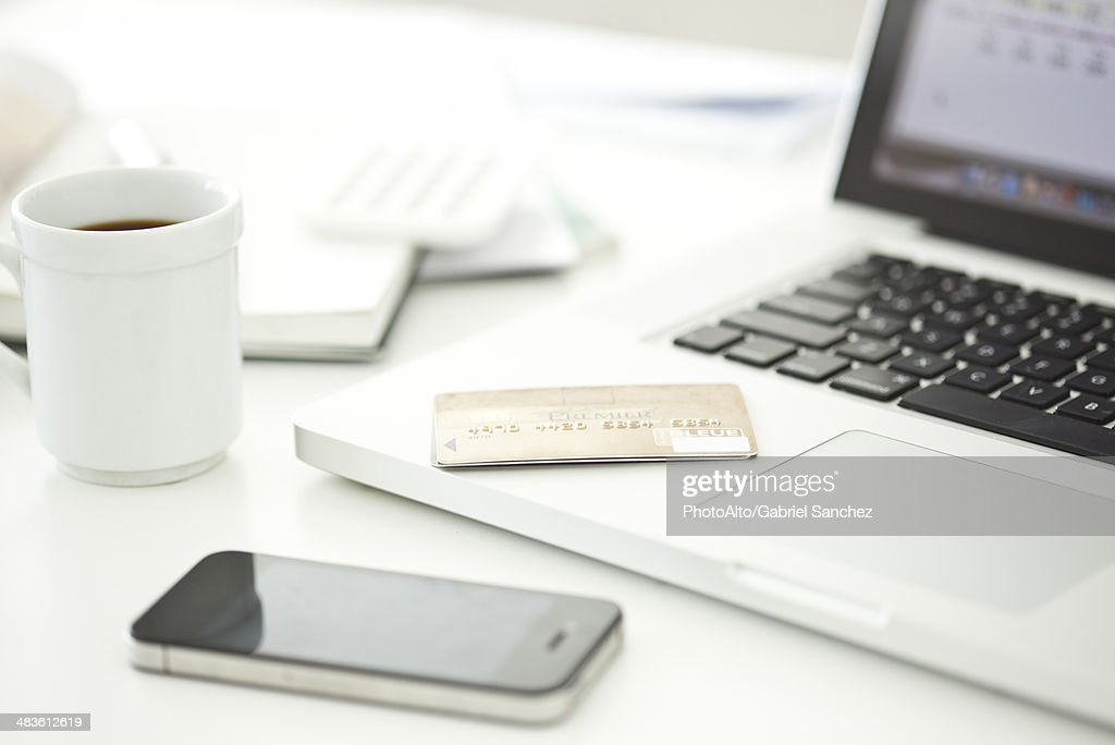 Credit card resting on laptop computer, smartphone and cup of coffee nearby : Stock Photo