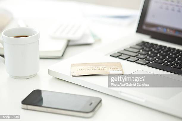 Credit card resting on laptop computer, smartphone and cup of coffee nearby