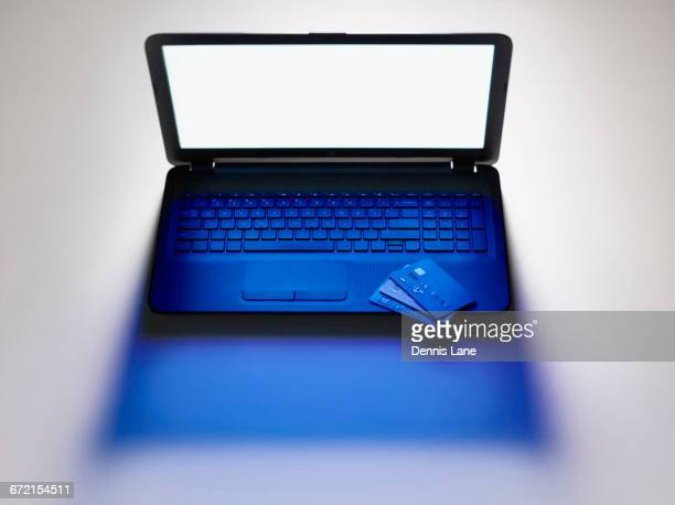 credit cards on laptop computer - identity theft stock pictures, royalty-free photos & images