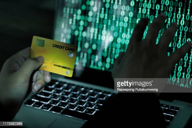 credit cards theft concept. hacker with credit cards on his laptop using them for unauthorized shopping - the shop la tienda del espia fotografías e imágenes de stock