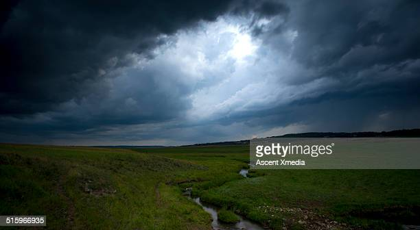 Creek descend through grassland landscape, ominous