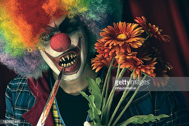 Creepy Clown carrying plastic flowers and bloody knife