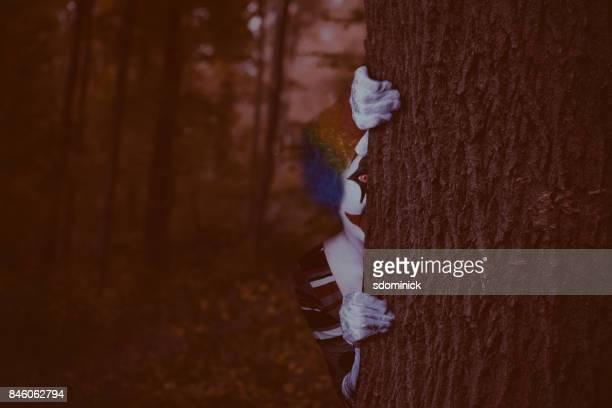 creepy clown peeking around tree - clown stock pictures, royalty-free photos & images