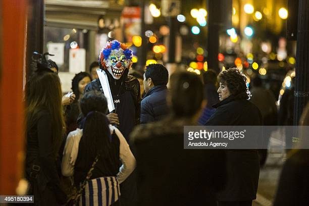 A creepy clown walks down the sidewalk during Halloween in the Georgetown neighborhood of Washington USA on October 31 2015