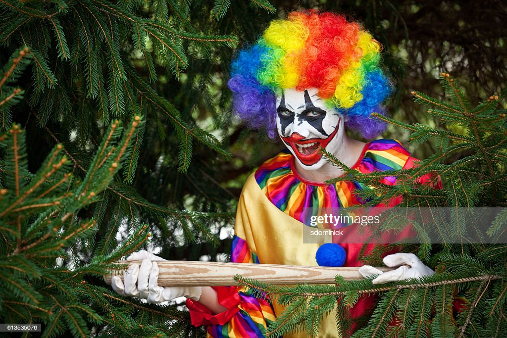 Creepy Clown With Bat Hiding In Pine Tree : Stock Photo
