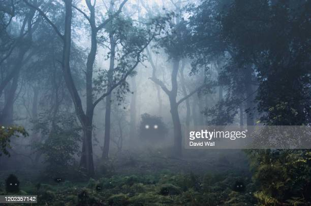 a creepy, fantasy forest of trees, back lighted with spooky, glowing eyes of creatures in the undergrowth. - monster fictional character stock pictures, royalty-free photos & images