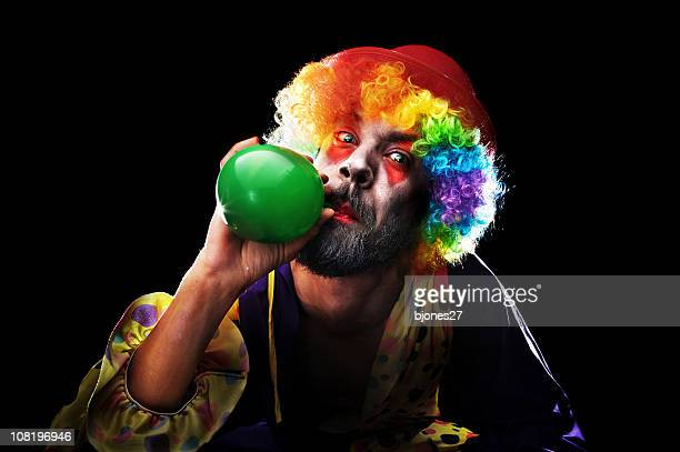 creepy looking clown blowing up balloon on black background - scary clown makeup stock photos and pictures