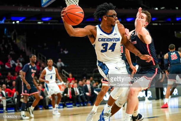 Creighton guard/forward Denzel Mahoney passes the ball around St Johns guard/forward David Caraher during the game between the St Johns University...