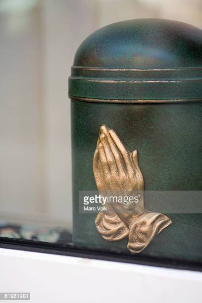 A cremation urn with praying hands on it