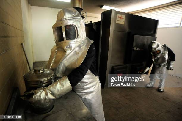 Cremation workers wear protective gear while prepare the furnace at Nezahualcoyotl cemetery before receiving a body that died due SARS Cov2 that...