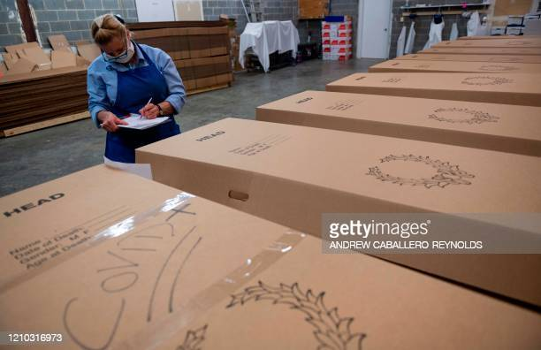 Crematorium supervisor Ginger Rowley checks names on cardboard caskets containing bodies to be cremated at the Maryland Cremation services in...