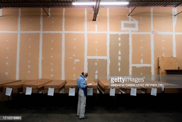 Crematorium supervisor Ginger Rowley checks the names on cardboard caskets containing bodies to be cremated at the Maryland Cremation services in...