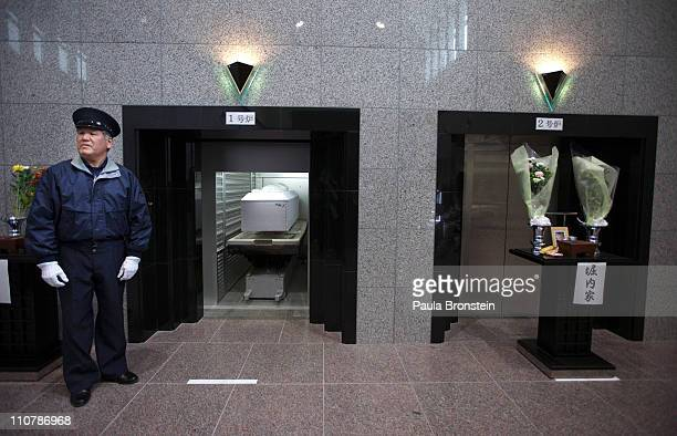 A crematorium worker gets ready to close the door with the coffin of Katsuko Oyama who was killed by the tsunami into the oven during a cremation on...