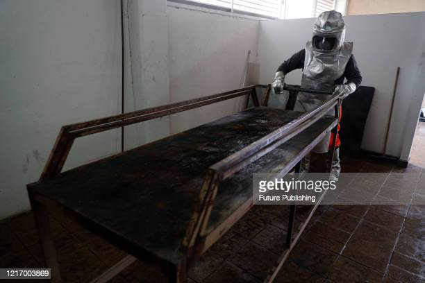 Crematorium worker of Nezahualcoyotl cemetery wears protective gear while prepares a place in the oven for cremation to the body of a person who died...