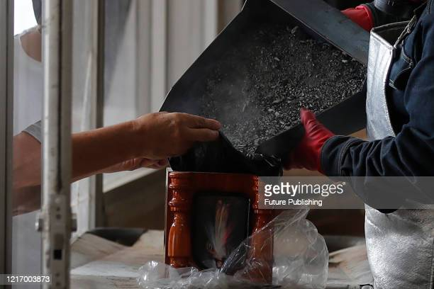Crematorium worker of Nezahualcoyotl cemetery wears protective gear while puts in a urn the remains of a person who died from COVID19 On June 2 2020...