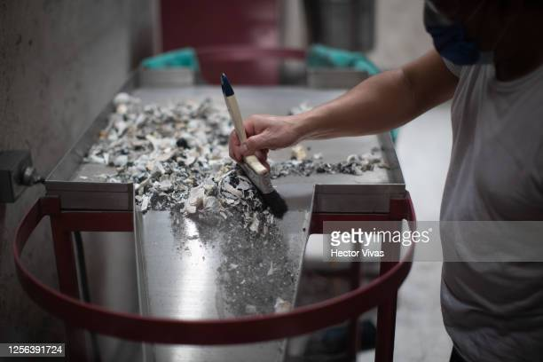 Crematorium worker places the ashes of a person who died from COVID-19 in an urn at the San Isidro Crematorium in Azcapotzalco on July 15, 2020 in...