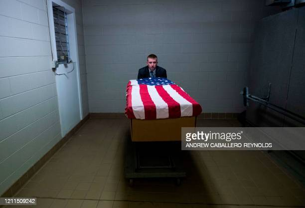 Crematory operator Brandon Cochran pushes a cremation box draped in a US national flag, containing the body a veteran who died of COVID-19, to an...