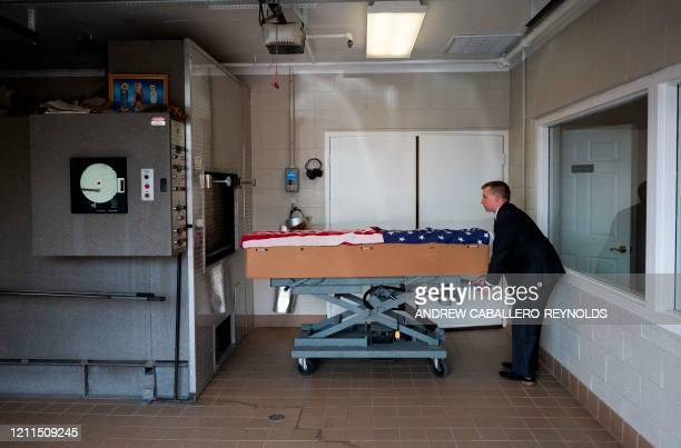 TOPSHOT Crematory operator Brandon Cochran pushes a cremation box draped in a US national flag containing the body a veteran who died of COVID19 to...