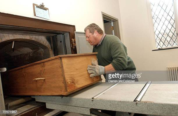 Crematory operator Joe Bancewicz places a coffin into the retort or cremation ovens at Mount Auburn Cemetary February 21 2002 in Watertown MA The...