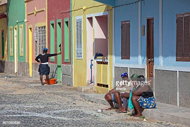 Creole women talking on doorstep in street in the village Sal Rei on the island Boa Vista Cape Verde / Cabo Verde Western Africa