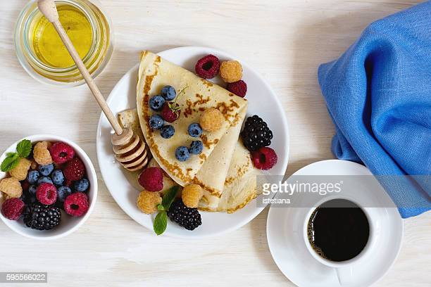 crepes with fresh berries served with honey and coffee for breakfast over rustic light  table viewed from above - crêpe pancake stock photos and pictures