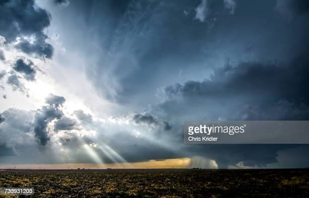 crepuscular rays through clouds around supercell thunderstorm, as it produces a large tornado just outside of dodge city, kansas, on may 24, 2016 - sturmbewölkung stock-fotos und bilder