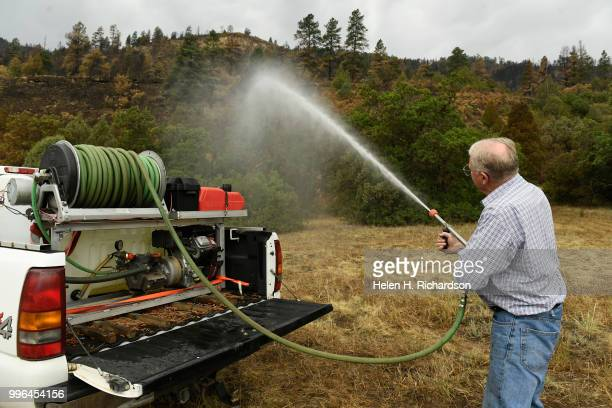 Cres Fleming demonstrates how he tried to put out the 416 fire as it started along the railroad tracks near his home on July 10 2018 near Hermosa...