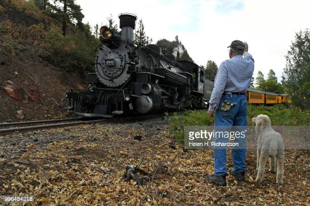 Cres Fleming with his dog Stella waves to Durango Silverton Train Locomotive 486 as it makes its way towards Durango on July 10 2018 near Hermosa...