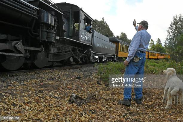 Cres Fleming with his dog Stella waves to the fireman driving the Durango Silverton Train Locomotive 486 as it makes its way towards Durango on July...