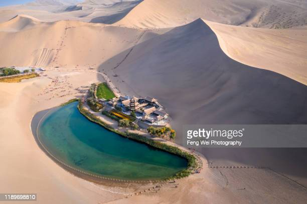 crescent lake with buddhist temple in kumtag desert, dunhuang, gansu china - gobi desert stock pictures, royalty-free photos & images