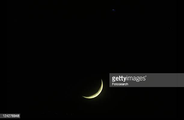 A crescent moon against a black starless sky