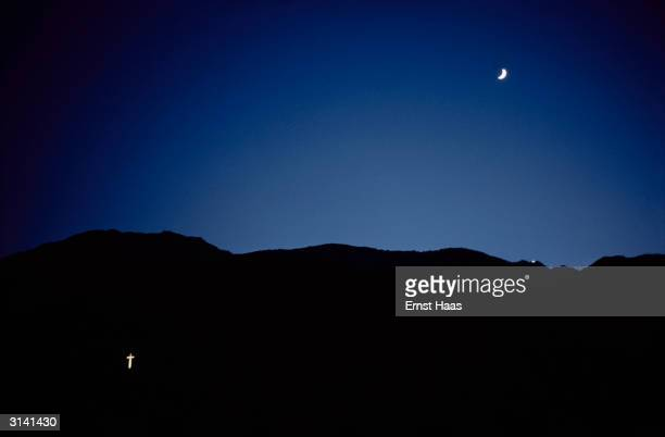 A crescent moon and a floodlit cross shine out through the darkness of Palm Springs an oasis city in the California desert Colour Photography book...