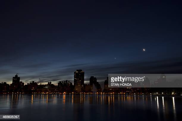 Crescent moon and Venus rise in the pre-dawn hours over the east side of Manhattan January 28, 2014 in New York in this view across the reservoir in...