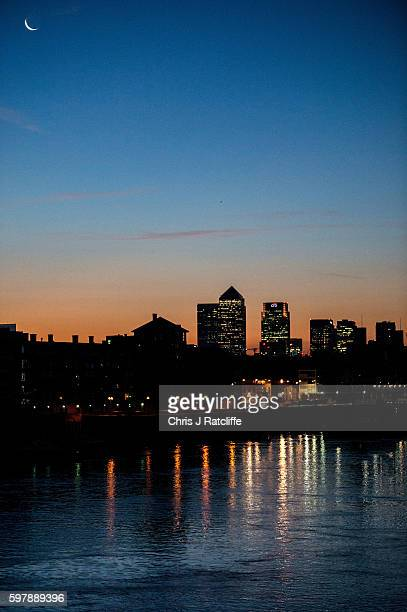 A crescent moon hangs over the financial district of Canary Wharf as dawn breaks and the sun rises over the British capital city on August 30 2016 in...