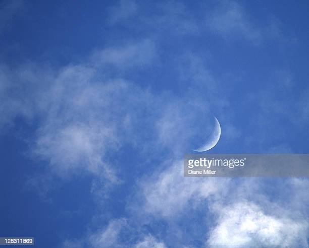 Crescent moon in blue sky with clouds