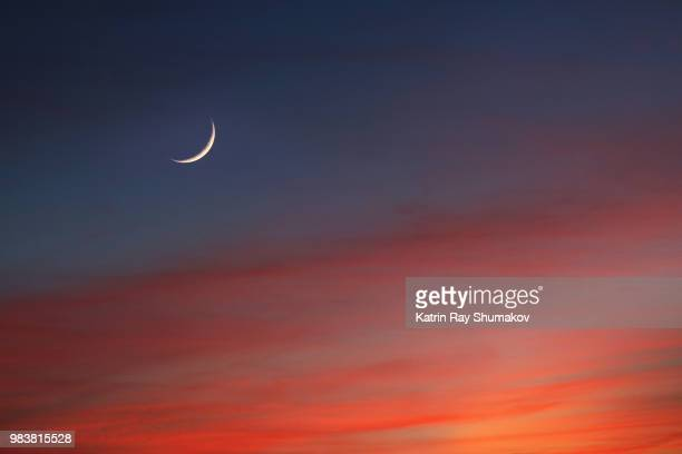 crescent moon in glowing sunset skies - semicírculo - fotografias e filmes do acervo