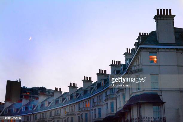 a crescent moon over clifton crescent, a row of victorian buildings in folkestone, england. - bo zaunders stock pictures, royalty-free photos & images